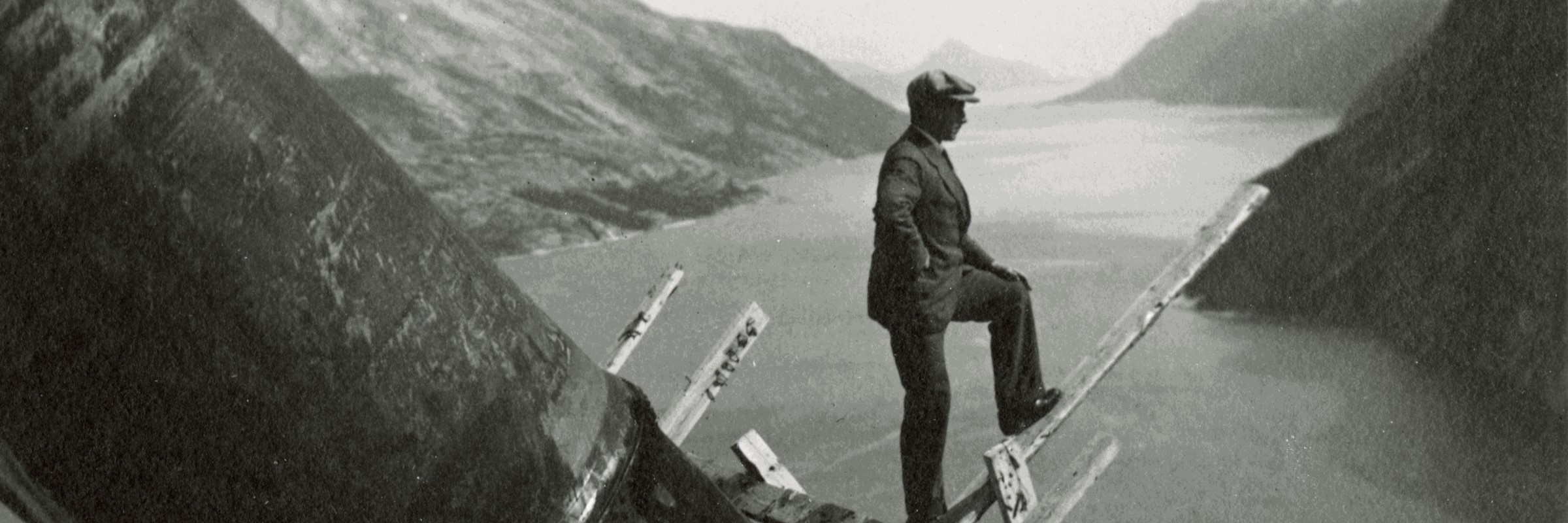 Black and white image of man looking out over a fjord
